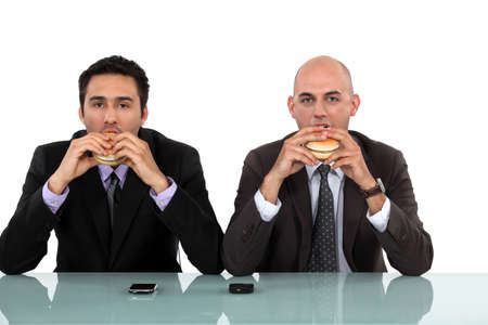 bald man: Two businessmen enjoying a burger.