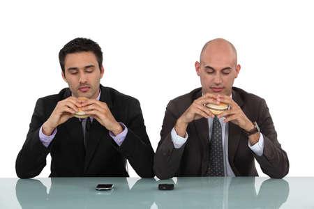 masticate: Two businessmen enjoying hamburgers