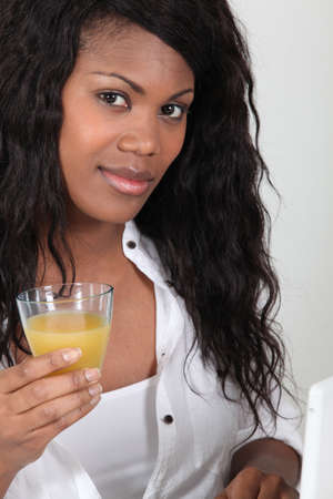 Woman drinking a glass of orange juice Stock Photo - 18471736