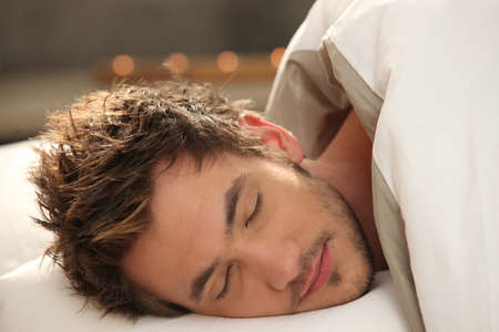 sleep well: Handsome young man asleep in bed Stock Photo