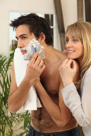 bathroom women: Young man shaving with his girlfriend watching