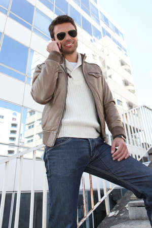 Fashionable man standing outdoors on phone photo