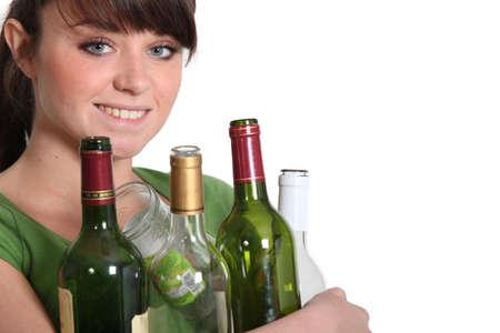reprocess: Woman recycling glass bottles
