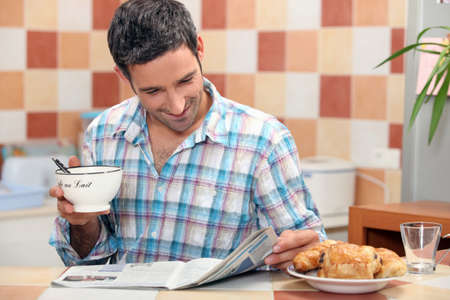 Man reading a magazine at the breakfast table photo