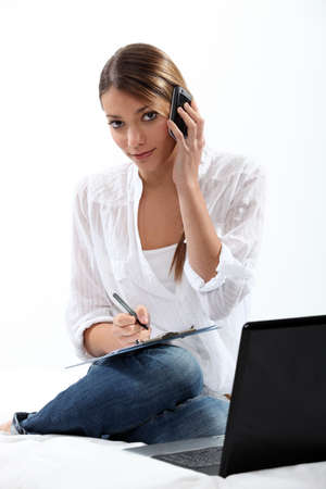 Woman with phone, laptop and clipboard Stock Photo - 18740772