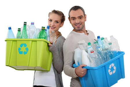 Couple recycling empty plastic bottles photo