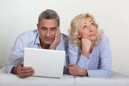 mid adult female: Middle aged couple with a laptop on their bed.