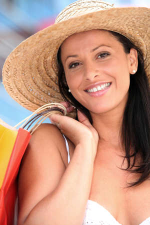 Woman in straw hat holding shopping bags photo