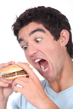 exaggerated: Young man taking an exaggerated bite out of a hamburger