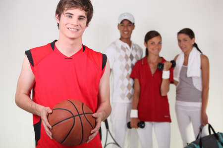 high: A basketball player posing with other athletes Stock Photo