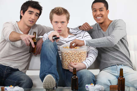 Three male friends watching television together photo