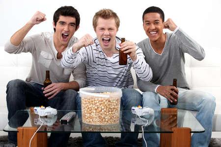 personas viendo television: tres adolescentes que tienen un partido en casa Foto de archivo