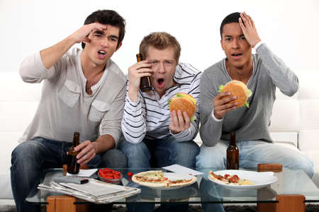 televised: Three lads cringing at the television Stock Photo