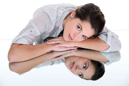 mirrored: Woman leaning on a mirrored table Stock Photo
