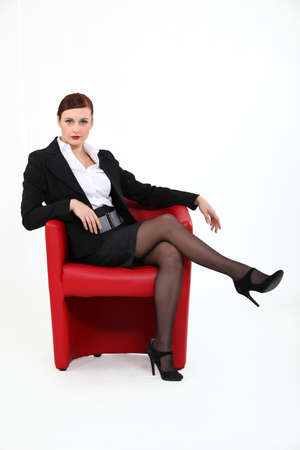 Woman sitting in red chair photo