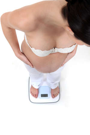 Pregnant woman weighing herself photo