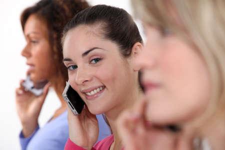 mobiele telefoons: Drie vrouwelijke vrienden op mobiele telefoons Stockfoto