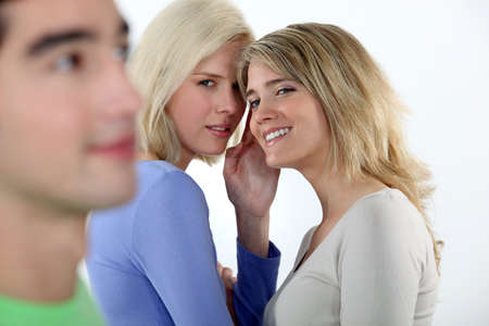 eligible: Young women gossiping about a man Stock Photo