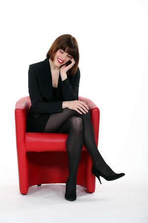 tacones negros: Mujer atractiva que usa un teléfono