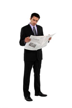 newspaper reading: Businessman stood reading the newspaper