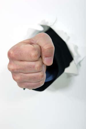 delito: Un puño que golpea a través de una pared