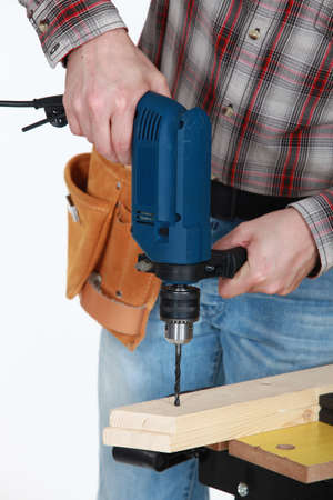 cordless: Man drilling through plank of wood