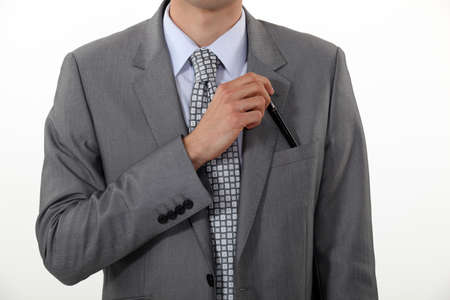 Businessman putting a pen in his pocket photo