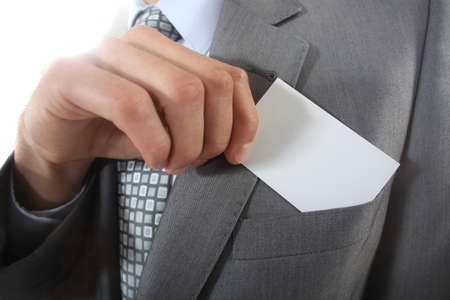 Businessman pulling a business card out of his pocket photo