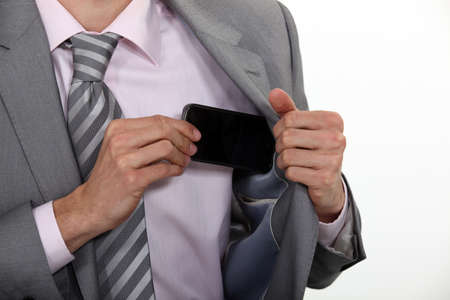put away: Businessman putting his mobile phone into his pocket Stock Photo