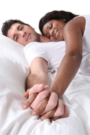 entwined: Couple holding hands in bed Stock Photo
