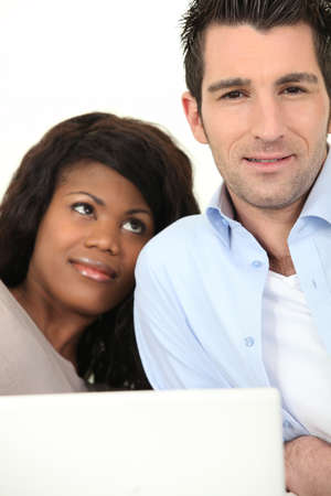 Relaxed couple in front of laptop photo