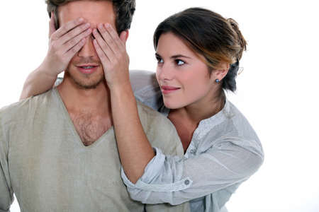 surprising: Young woman holding her hands over a mans eyes