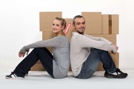 vacate: Couple sitting in front of cardboard boxes