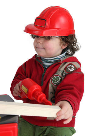 Little boy with toy drill pretending to be workman photo