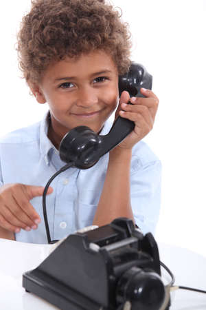 Young boy with an old-fashioned telephone photo