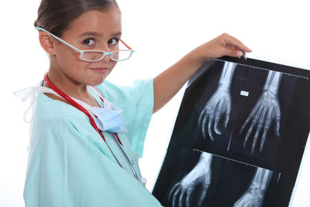 role play: Young girl dressed in hospital scrubs examining an X ray Stock Photo