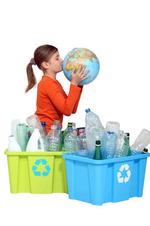 Young girl kissing the planet next to her recycling photo