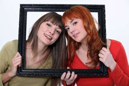 Women holding wooden frame photo
