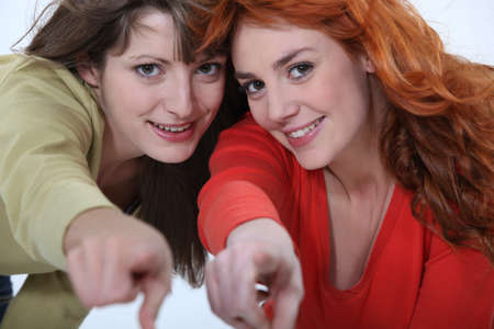 indicating: Two female friends pointing at the camera.