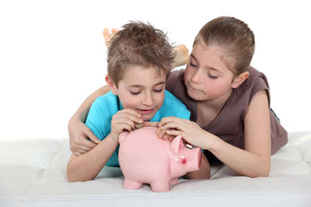 Kids putting coins in a piggy bank photo
