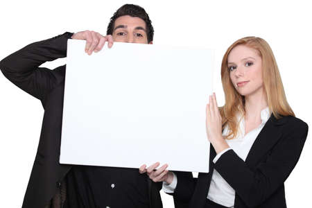 advertising board: businessman and businesswoman holding an advertising board Stock Photo