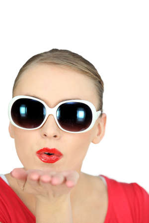 Woman with sunglasses blowing kisses on white background photo