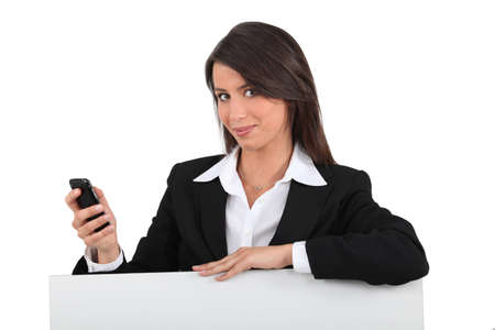 representatives: Businesswoman with mobile posing by blank poster