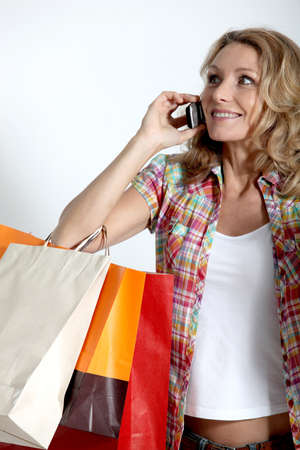 retail therapy: Blond woman holding shopping bags talking on cellphone