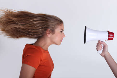 wind blown hair: Girl with hair blown backwards by megaphone Stock Photo