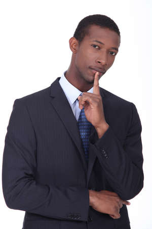 cogitate: Businessman with his finger to his chin in thought
