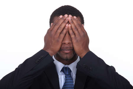 black man putting hands on his eyes photo