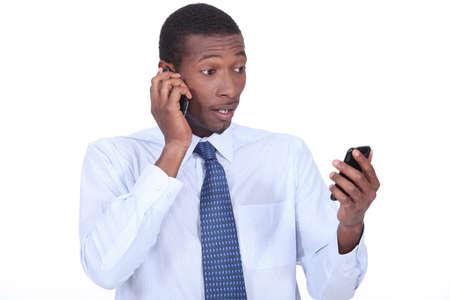 Shocked businessman holding two telephones photo