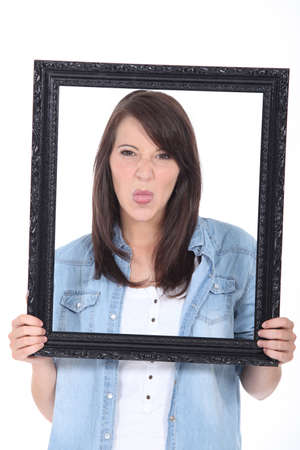 young woman holding a picture frame and sticking out her tongue photo