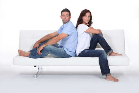grabbing at the back: Couple back to back on white sofa